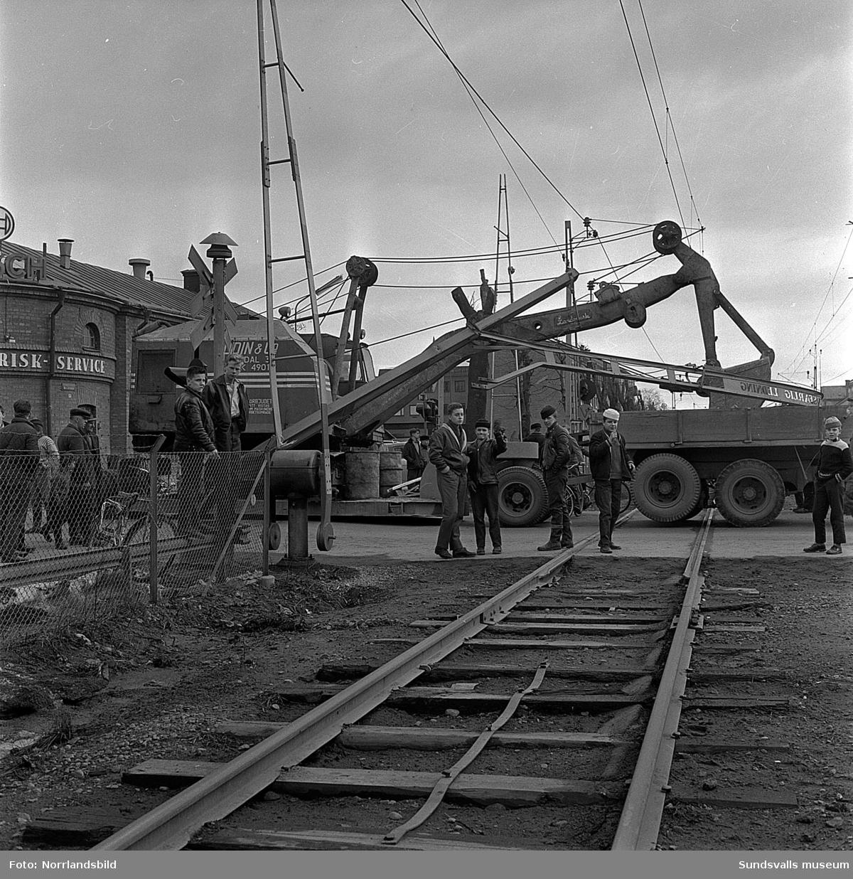 En trailer med en grävmaskin på rev ned överliggaren, men missade med en hårsmån kraftledningen, vid järnvägsövergången på Skolhusallén.