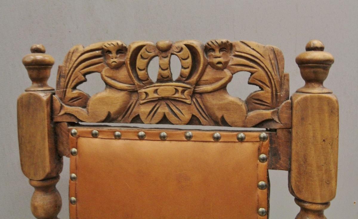To nakne barnefigurer (eller havfruer?) samholder en stor krone. Motivet avsluttes på begge sider av et blad.
