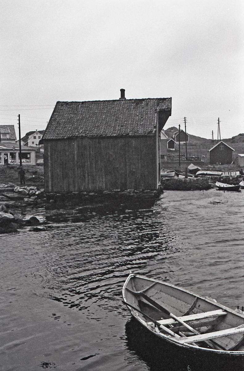 Mikael Klovnings sjøhus - Eksteriør fasade sør. Mikael Klovning står på vestsida. Til høyre kan en se butikken. I forgrunnen ligger en færiing.