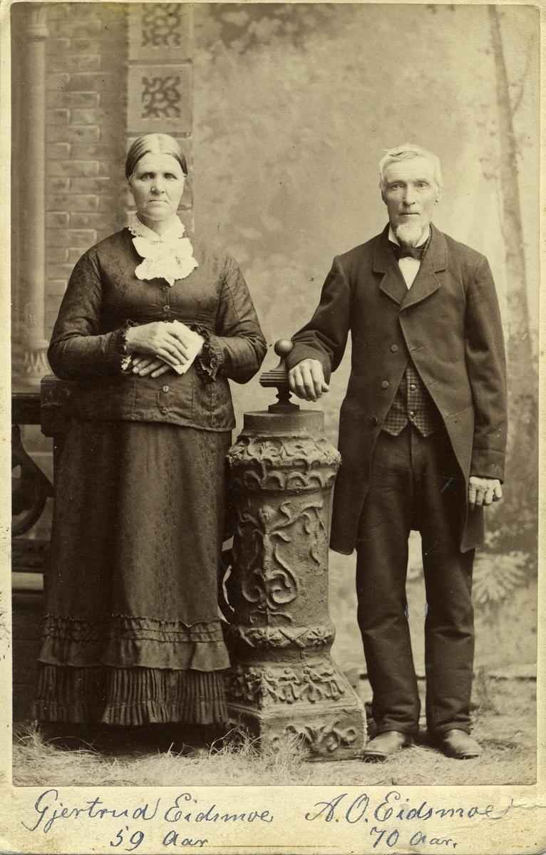 Portrett av en eldre kvinne og mann. Begge står i et studio og  begge er iført finklær.
