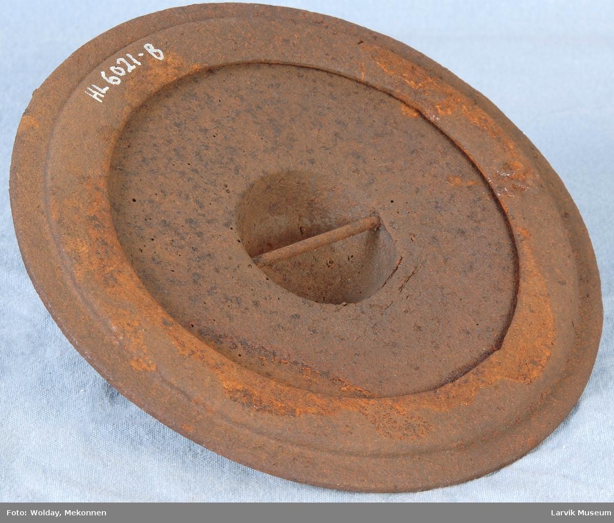 Rundt lokk til jernovn, ant. etasjeovn, nedsunket håndtak/grep danner en kule på baksiden. Ring