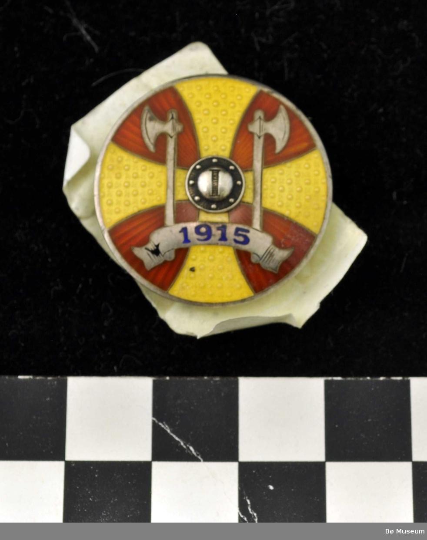 "Sirkelformet medaljeknapp med to økser og ""1915"" på banner i forkant"