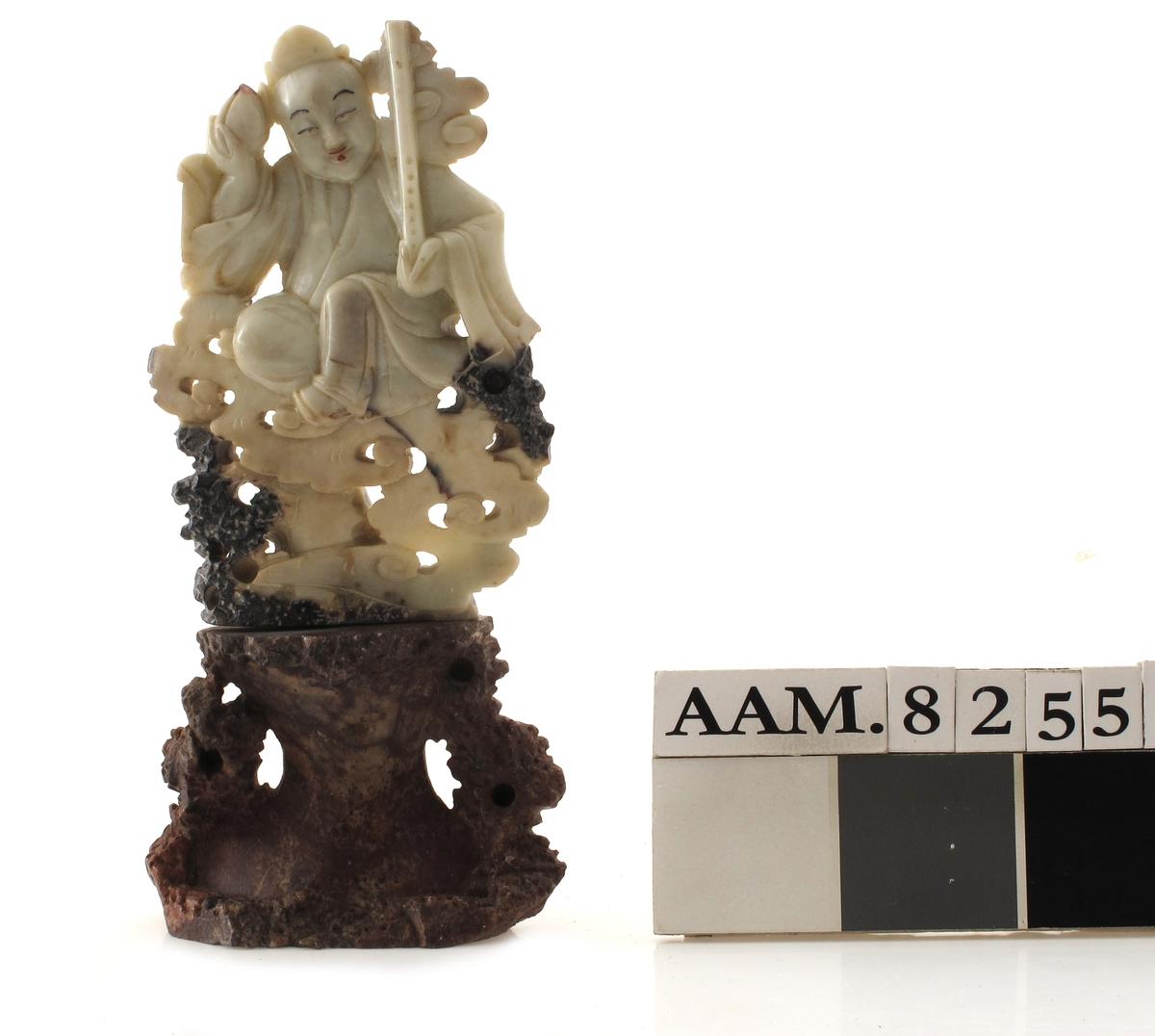 Gudebilde, skåret i alabast. Skåret ut av to stykker marmor, satt oppå hverandre. Øverste del av hvit marmor med noe sort, nedre  del av rødbrun marmor.