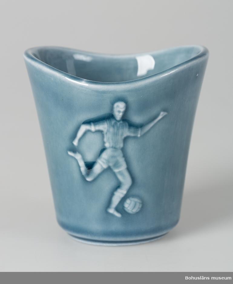 """Liten vas konande nedåt. Glaserad i blågrått.  Reliefdekor av fotbollspelare, en fotboll, tretton olika nationsflaggor samt texten: """"VM 1958."""" En match under detta världsmästerskap i fotboll spelades söndagen den 8 juni 1958 på Rimnersvallen i Uddevalla. ."""