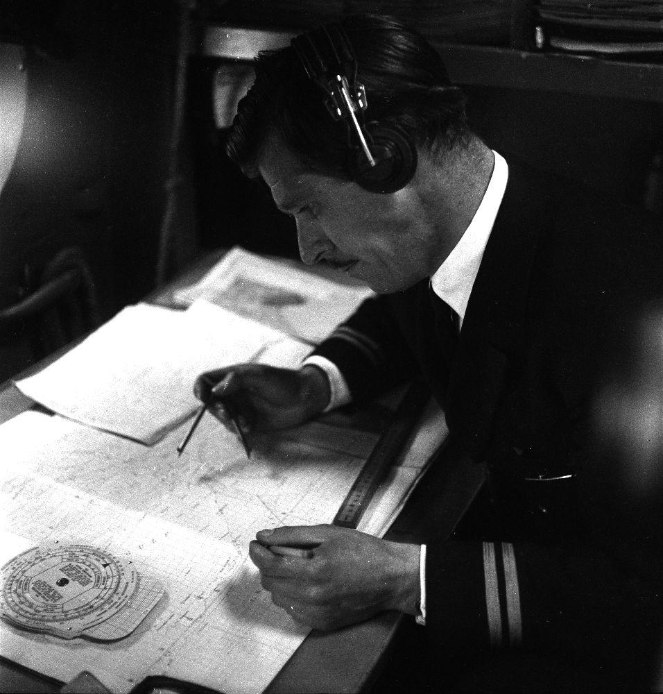 Luftfoto. Før Braathens SAFE startet sin prøverute til Østen ble det mange stopp underveis. En person, navigatør, flymannskap, sitter på sin plass og beregner reiseruten til neste destinasjon.