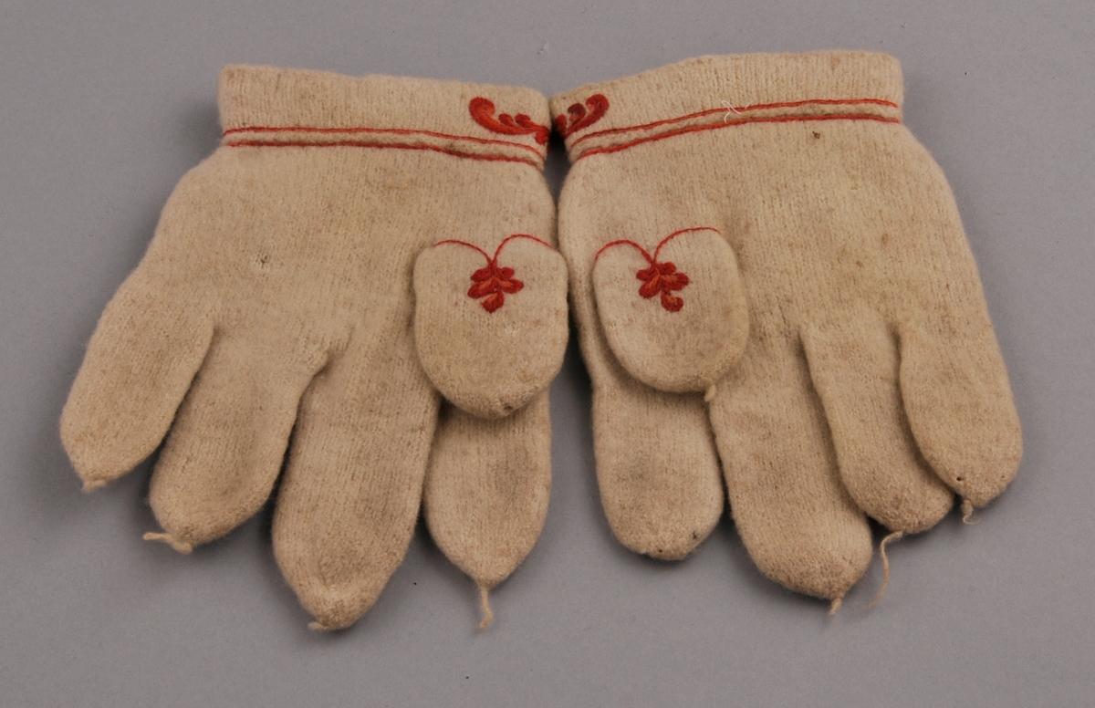 Kvite, rosesauma fingervottar i heimspunne garn. Rosesauma på handbaken, manskjetten og tommelen med blankt, kjøpt ullgarn. vottane har trådendar på fingrane.