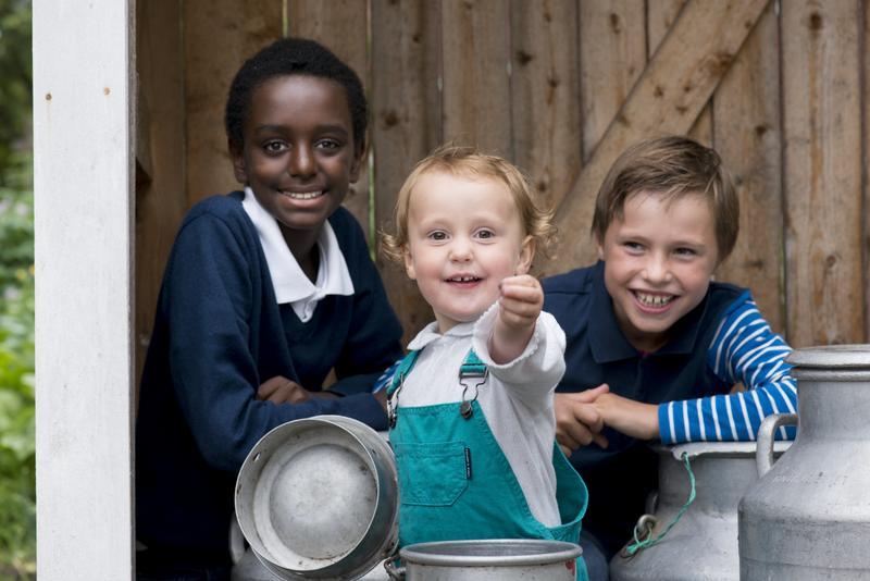To gutter og en baby sitter i melkrampen bak tre melkespann