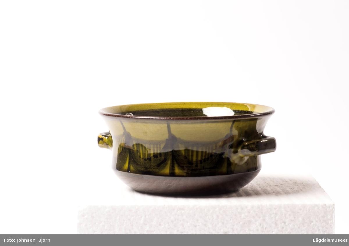 Olivengrønn skål med ornamenter langs kanten.