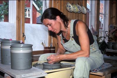 Kvinnelig kjeramiker former kjeramikk på dreieskive.