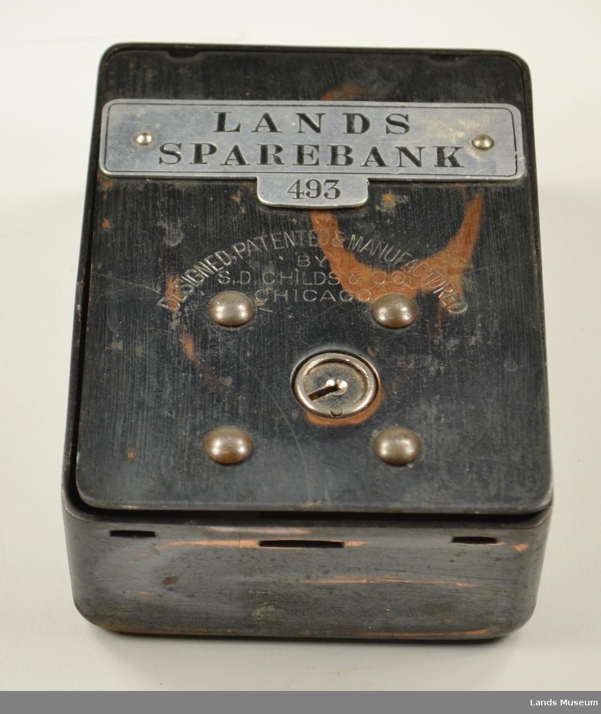 Sparebøssa har eit låsbart lokk framme. På toppen er det to hull, eit avlangt til mynt og eit rund til sedler.