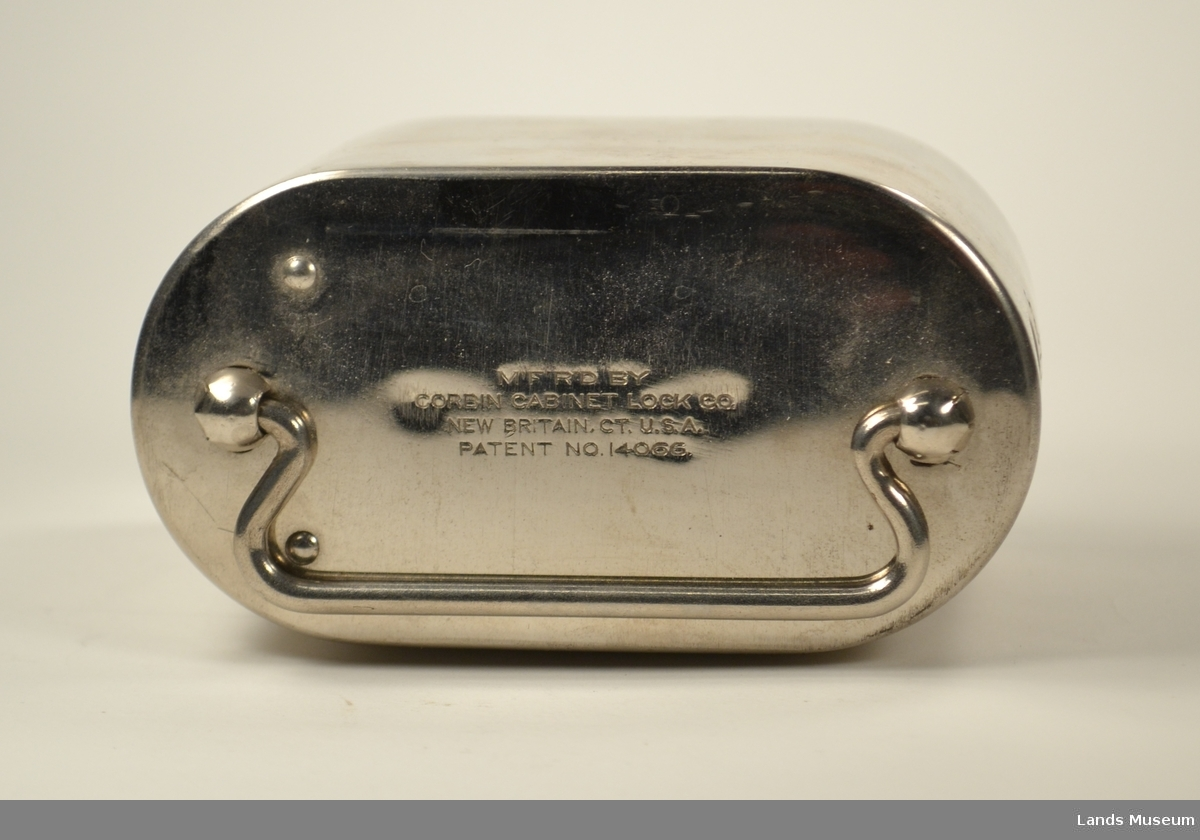Kisteform med hank. Avlangt hull for mynter på den eine kortenden og rundt hull for sedler på den andre kortenden. Låsbar bunn.