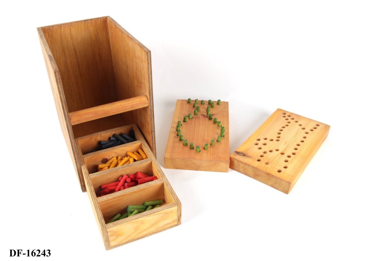 Pedagogisk lek og test av finmotorikk.  Kasse med rundt håndtak. I kassen er det to spillbrett med hull, til å sette i spillpinner som finnes i fire ulike farger (grønn, rød, gul og blå). Spillpinnene er oppbevart i en eske med fire kammer, et til hver av fargene.