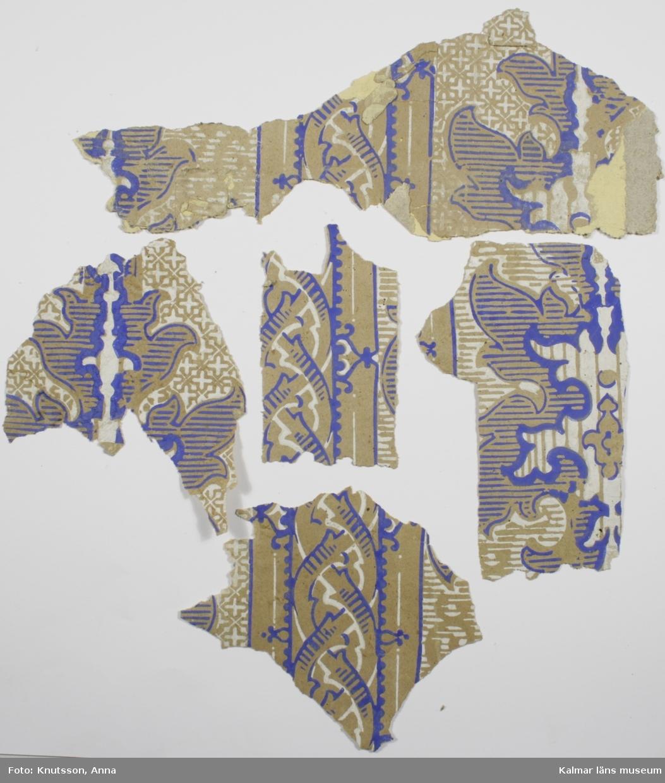 KLM 43872:2 Tapet i papper. 5 bitar. Oblekt pappersbotten med olika lodräta mönsterkombinationer, bland annat medaljonger och flätningar i ultramarinblått och vitt. På baksidan sitter rester av KLM 43872:3.