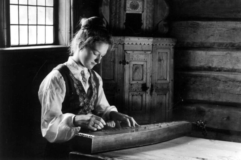 En unge jente i Valdresbunad spiller langeleik i Hålistua fra Vang. 1962, (Foto/Photo)
