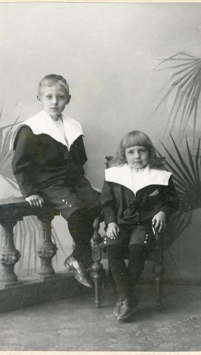 To barn avbildet sittende på en stol og gelender. Begge er iført jakker med store slag.
