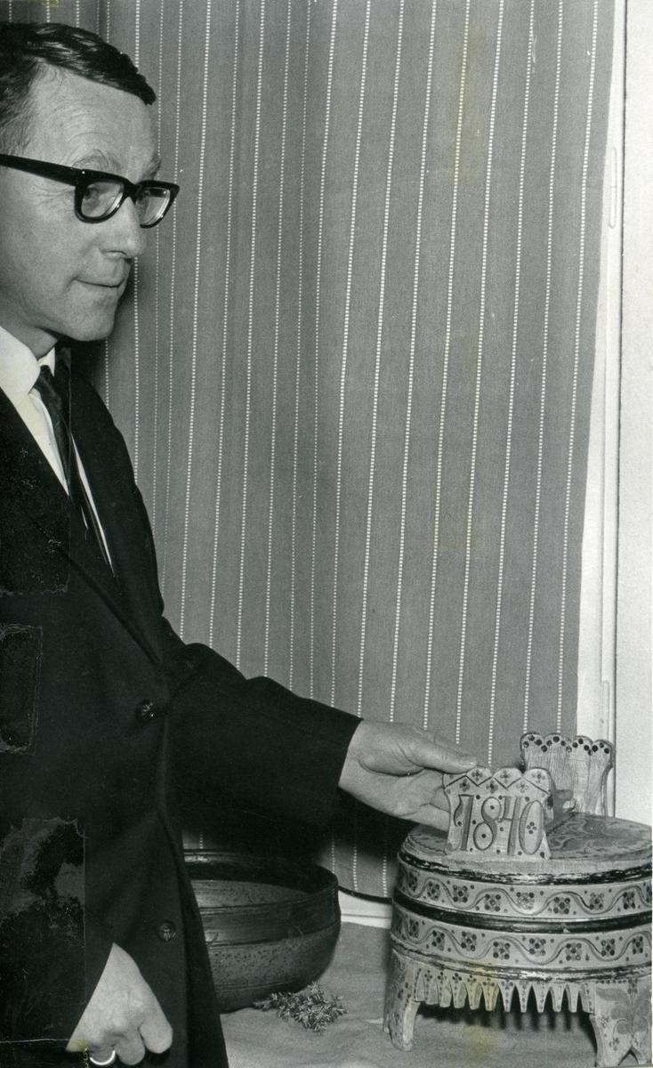 Prospektkort av Trygve Bjørgo. Han holder i en rosemalt tine. Bildet er tatt ved en lærerlagsfest i Reinli.