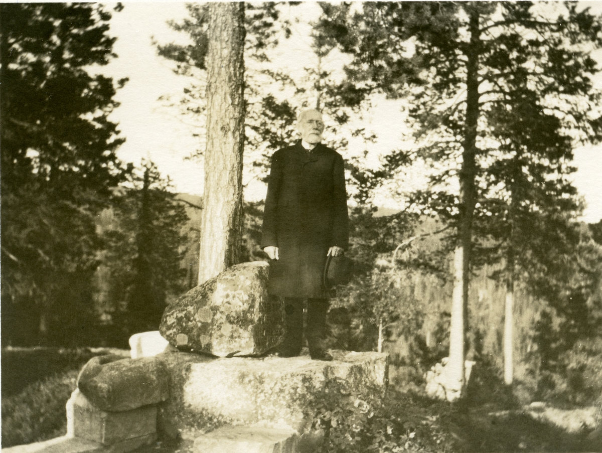 """Prospektkort av Thomas Barth. Han står ved """"prekestolen"""" på Vatneberget i Hedalen."""