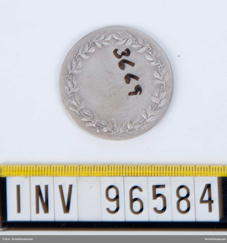 Medalj i silver för Skånska kavalleriregementet. Stans 14513, härdad 1942-10-21. Medalj, storlek 40 mm diameter, åtsida med tre standar inom omskrift KUNGL. SKÅNSKA KAVALLERIREGEMENTET 1928 1942, enligt modell av skulptören Karl Hultström.