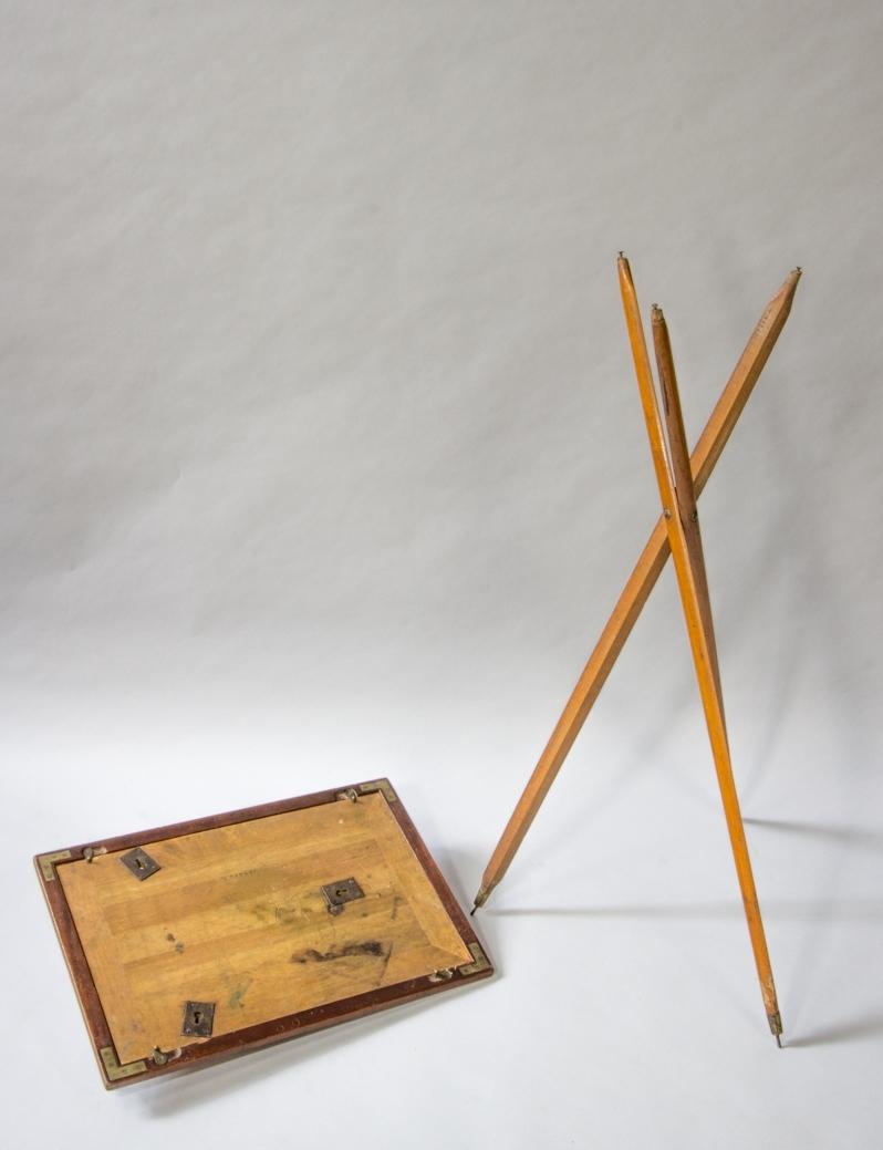 Stativ av mahogny bestående av tre ben om förs in i tre nyckelhålsliknande beslag på den plana skivans undersida. Hopfällbart.