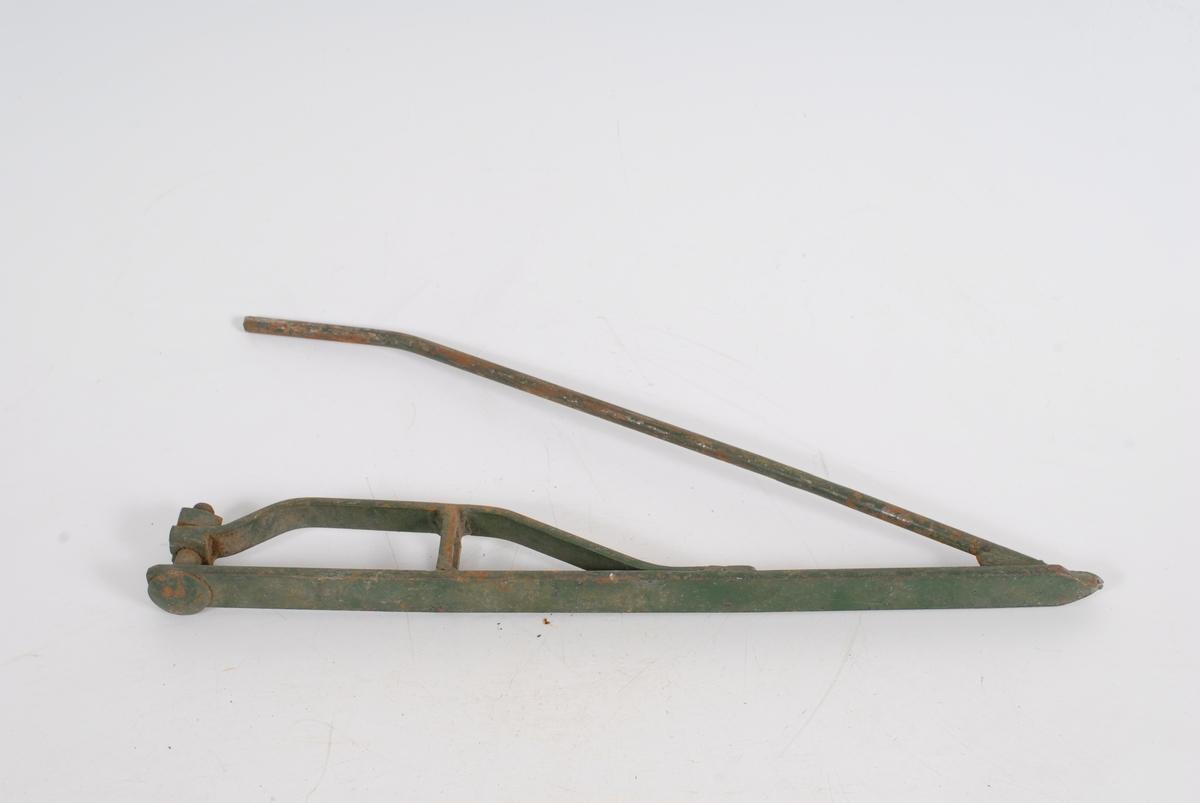 Teknikk: Malt. I forkant p}sveiset en jernstang som danner en vinkel til foten på 30 grader, bakkant er bøyd så den går paralelt med foten. En bolt er skrudd gjennom bak på foten og ut fra denne en parallell skinne som ligger lavere enn stangen og er festet foran. 13 CM lengre fremme hviler skinnen på en stol som er festet til foten. Skinnen buer så jevnt ned mot foten der den 15 CM lengre fremme er sveiset fast. Form: Liggende fot til å vri gresset bort fra bladet.