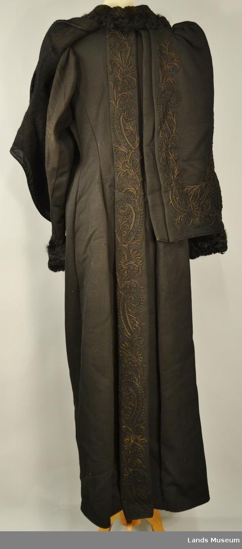 Kåpen er helforet med silkefor. Den består av kåpe med en fastmontert cape. Den er dekorert med lissebroderier i silke på krage og cape.