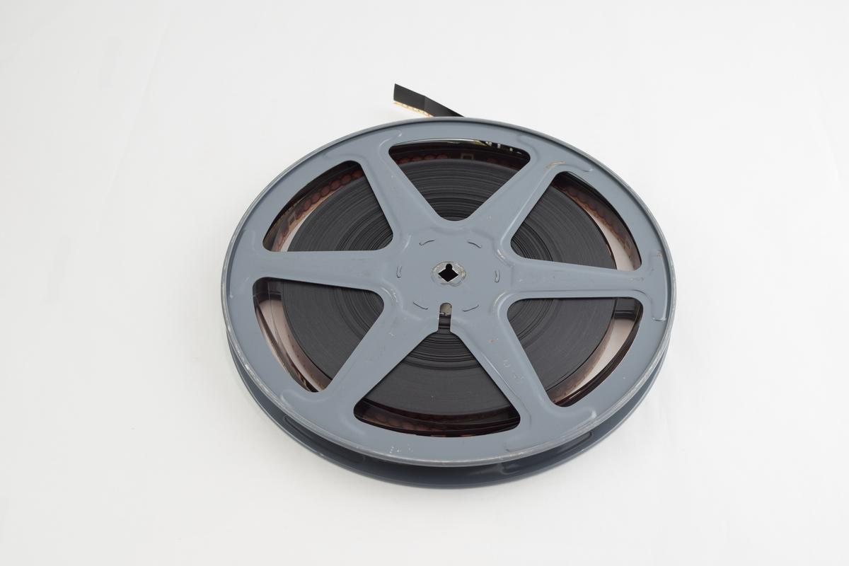 Filmrull i eske. Film på metallspole. Firkantet papiretui åpnes langs en av sidekantene, festes med metallspenne. Delvis avrevet etikett på baksiden.
