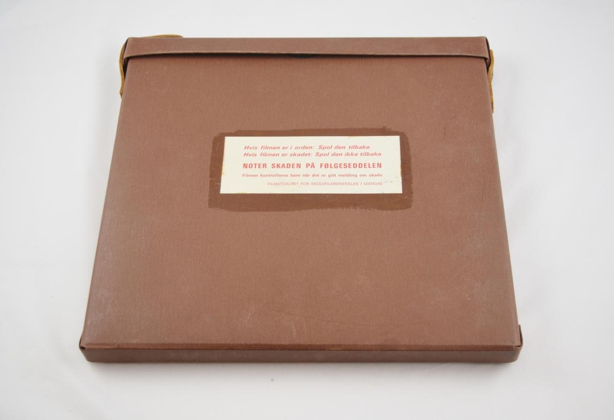Filmrull i eske. Film på metallspole. Kvadratisk papiretui i to deler, lukkes langs den ene siden ved hjelp av lærreimer og metallspenner. Mye informasjon på etikett.
