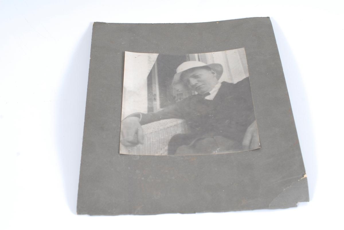 Ung mann i kurvstol utenfor et hus (man ser et vindu eller en dør i bakgrunnen). Han sitter med armen på lenet og ser henslengt ut, og på hodet har han en hvit sommerhatt.
