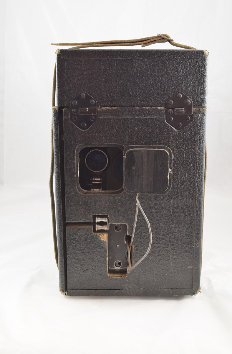 Filmfremviser til filmruller. Filmen tres gjennomapparatet som vist på arket på eskens innside. Rektangulær koffert rundt apparatet med luker som kan åpnes der det er behov. (Høyttalere kommer i tillegg - se referanser.)