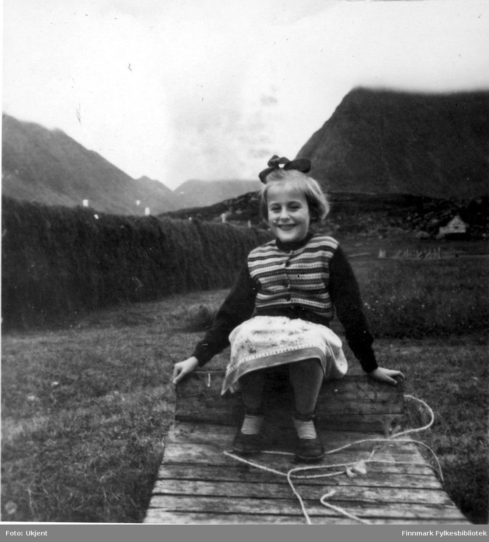 Randi Martinsen sitter avbildet i Nuvsvåg i 'slåttonna' omkring 1954. Hun har på seg genser, skjørt og strømper. Og på hodet har hun en hårsløyfe.Ved siden av henne kan man se et tau og i bakgrunnen ser man blant annet fjell.