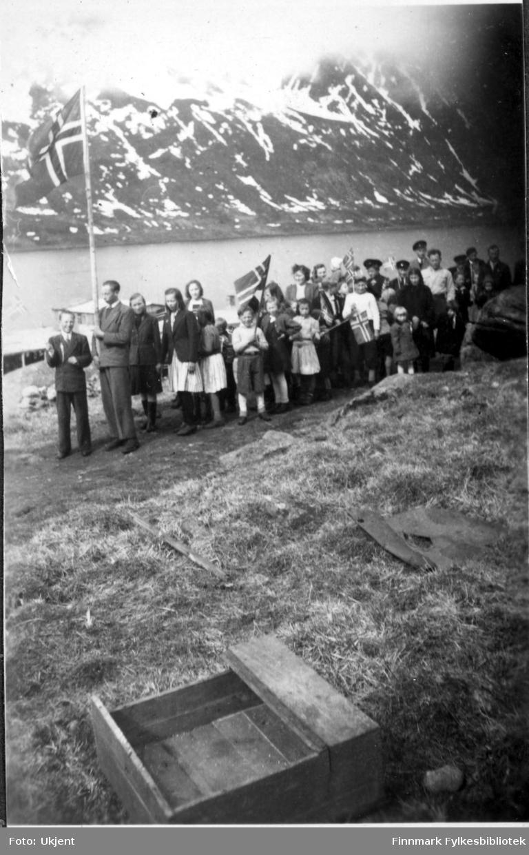 17.mai feiring i Nuvsvåg etter frigjøringen. Fotografiet tatt på slutten av 1940-tallet. Barn går i 17.mai tog med norskeflagg. Barna er kledd i skjørt, luer, bukser, gensere,jakker og sko. En mann i dress holder på et stort flagg helt framst i toget.