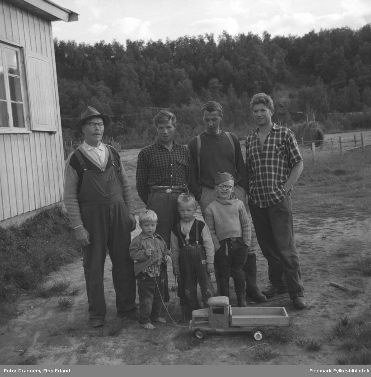 Fire menn og tre gutter fotografert på gårdsplassen ved langveggen til et hus. De er fra venstre, Alfred Karikoski, Aage Karikoski, Jacob Karikoski, og Oskar Karikoski. Navnet på guttene foran er ukjent.