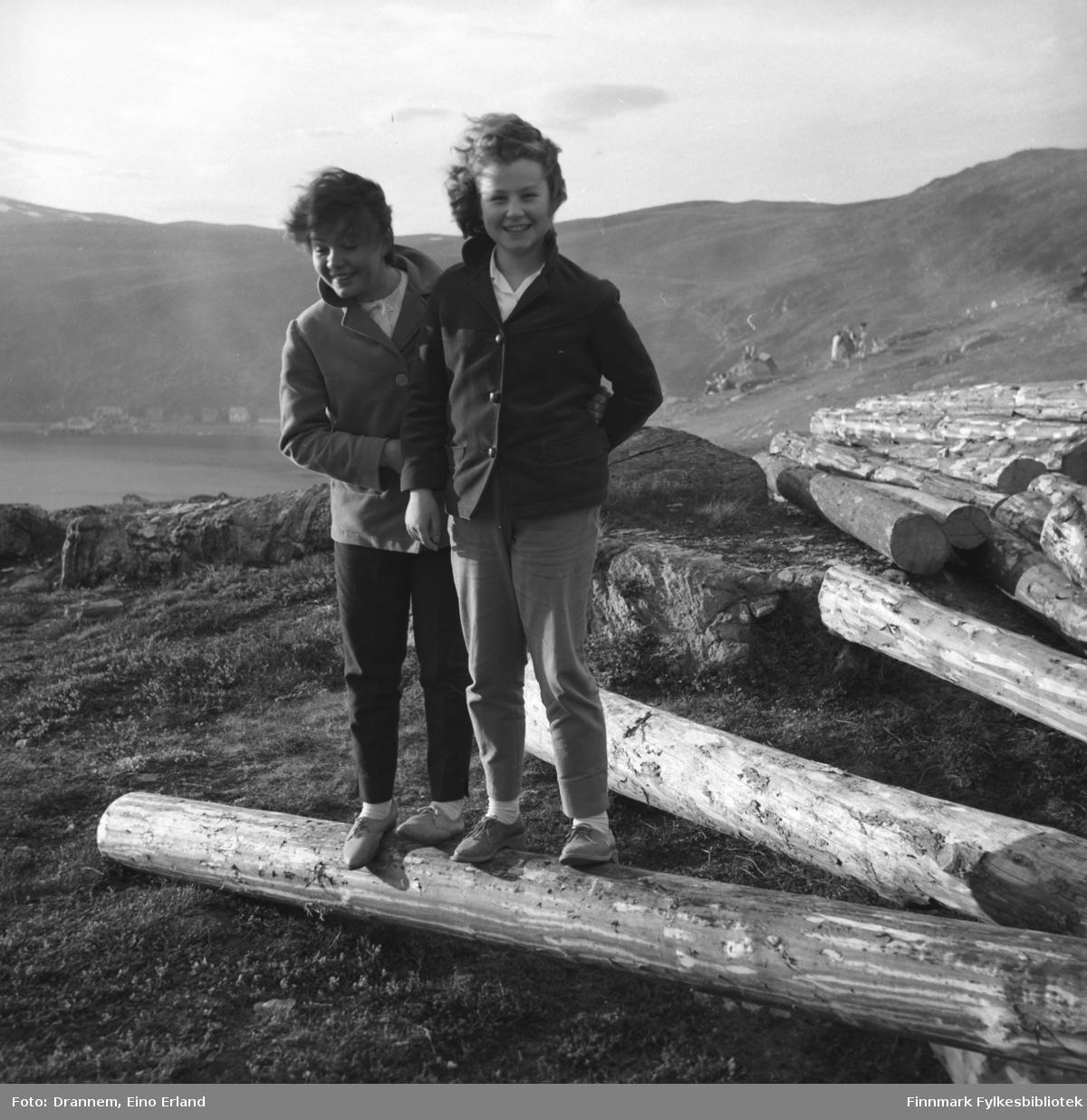 To jenter står på tømmerstokker som skal bli snøskjermer på fjellet Salen i Hammerfest. De er Maija etternavn ukjent og Turid Karikoski.