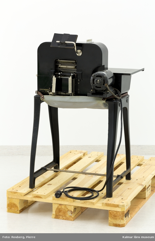 KLM 28585:1. Hålkortsmaskin, stansmaskin. Användes för stansning av hål i hålkorten. Stansmaskin av svartlackerad metall på fyra ben. Till höger ett tangentbord, i mitten utrymme för hålkort samt stansar. Undertill en plasthuv för uppsamling av de utstansade pappersbitarna. Maskinen var troligen från början helt mekanisk men har senare elektrifierats och försetts med en motor som sitter på baksidan. Baktill en vinklad spegel som användes för att kontrollera att korten kom ut på baksidan av maskinen efter stansningen. Till vänster en knapp för påslagning och baktill en svart elsladd. På maskinen diverse fastskruvade metallskyltar samt ett klistermärke, samtliga med information om tillverkaren och produktionen, bl.a: POWERS SAMAS ACCOUNTING MACHINES ENGLAND. På baksidan en mindre mässingsskylt med instansat nummer: 0264. Till maskinen hör en skyddshuv i svart galon med text i guld: POWERS FOUR U.A.K.P.  Till maskinen hör en liten huv av svartlackerad metall som suttit på undersidan med samma funktion som plasthuven. I plasthuven låg diverse runda pappersbitar, dessa har samlats i en påse och förvaras med maskinen.