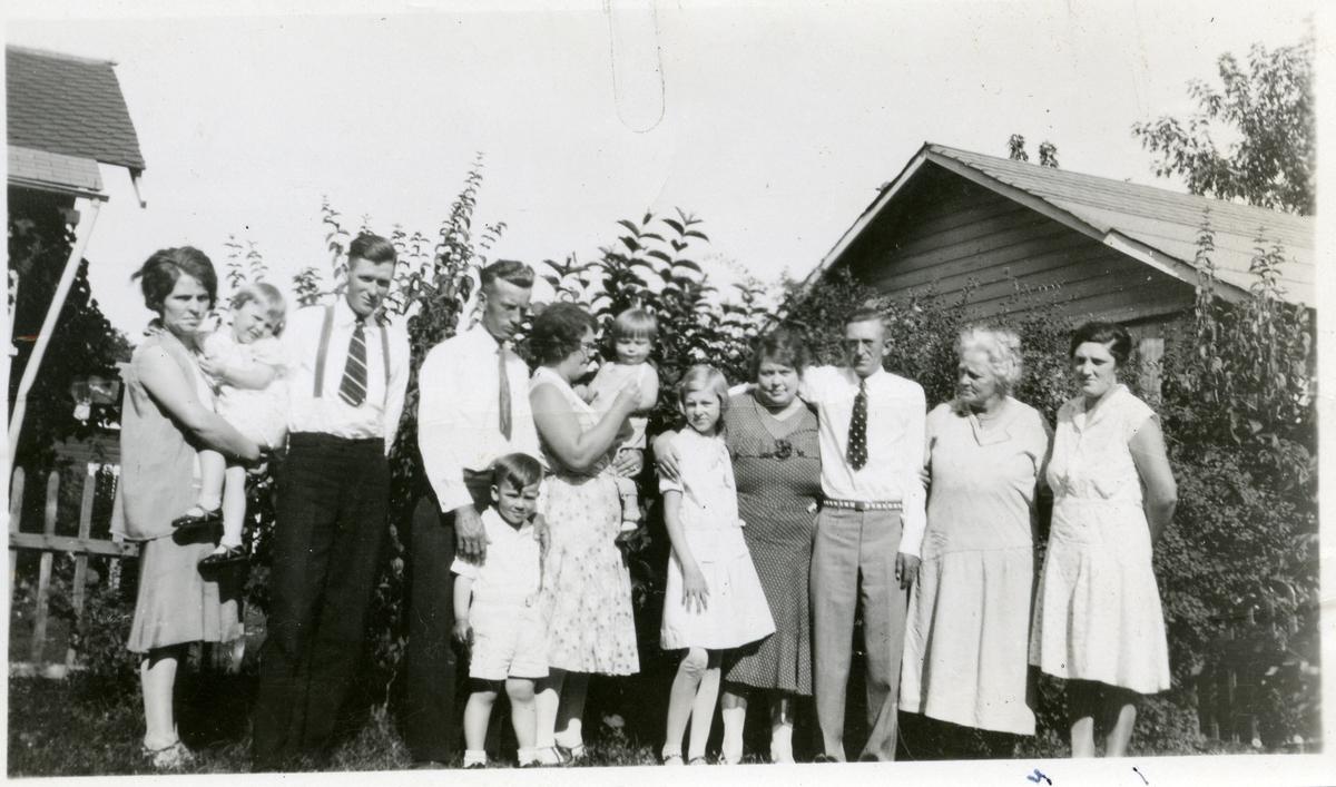 Gruppebilde flere kvinner, menn og barn som står oppstilt ved et gjerde. Alle er kledd i pent sommertøy og bildet er tatt i USA.