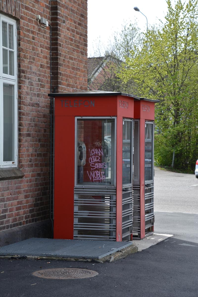 Telefonkioskene står ved Tønsberg jernbanestasjon, og er blant de 100 vernede telefonkiokser i Norge. De røde telefonkioskene ble laget av hovedverkstedet til Telenor (Telegrafverket, Televerket). Målene er så å si uforandret.  Vi har dessverre ikke hatt kapasitet til å gjøre grundige mål av hver enkelt kiosk som er vernet.  Blant annet er vekten og høyden på døra endret fra tegningene til hovedverkstedet fra 1933. Målene fra 1933 var: Høyde 2500 mm + sokkel på ca 70 mm Grunnflate 1000x1000 mm. Vekt 850 kg. Mange av oss har minner knyttet til den lille røde bygningen. Historien om telefonkiosken er på mange måter historien om oss.  Derfor ble 100 av de røde telefonkioskene rundt om i landet vernet i 1997. Dette er en av dem.