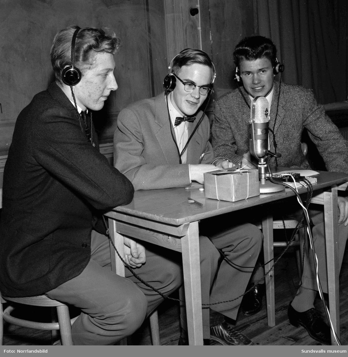 """Radiotävlingen """"Vi som vet mest"""" i läroverkets aula, en frågesporttävling för gymnasieelever med Folke Olhagen. Ett lag med tre grabbar före, och under, inspelningen samt publik och hejaramsa."""