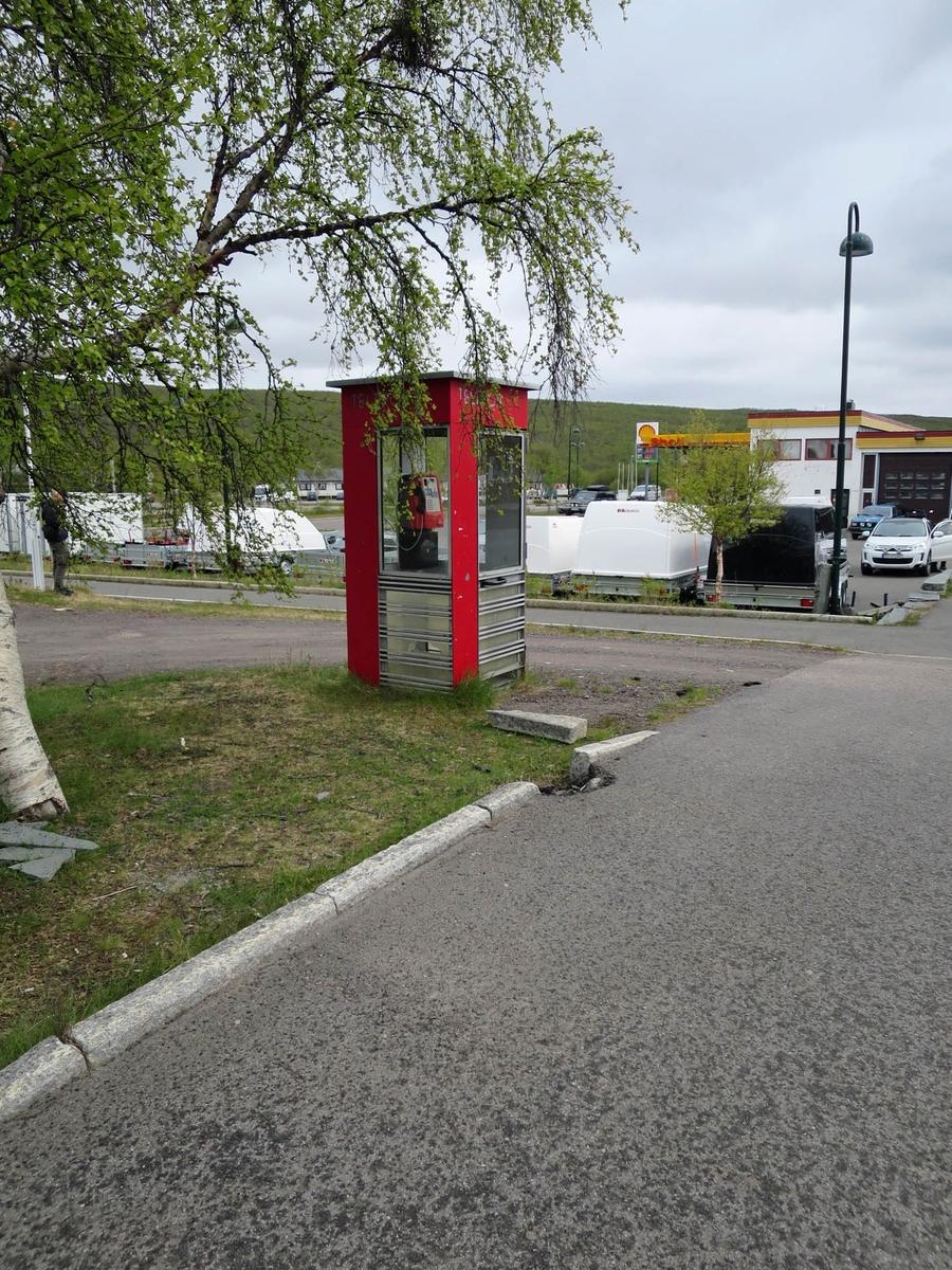 Denne telefonkiosken står i Rådhusveien 2 i Tana, og er en av de 100 vernede kioskene i Norge. De røde telefonkioskene ble laget av hovedverkstedet til Telenor (Telegrafverket, Televerket). Målene er så å si uforandret.  Vi har dessverre ikke hatt kapasitet til å gjøre grundige mål av hver enkelt kiosk som er vernet.  Blant annet er vekten og høyden på døra endret fra tegningene til hovedverkstedet fra 1933. Målene fra 1933 var: Høyde 2500 mm + sokkel på ca 70 mm Grunnflate 1000x1000 mm. Vekt 850 kg. Mange av oss har minner knyttet til den lille røde bygningen. Historien om telefonkiosken er på mange måter historien om oss.  Derfor ble 100 av de røde telefonkioskene rundt om i landet vernet i 1997. Dette er en av dem.