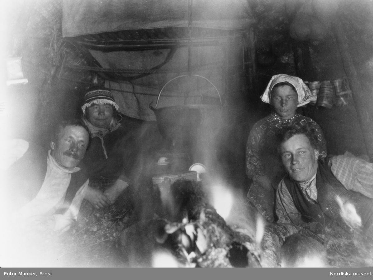 Vilhelm och Marja Prost (född Sevä, dotter till Per Sevä) med son och dotter på ömse sidor om arran (eldstaden) i kåtan.