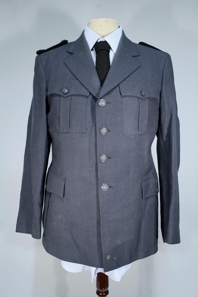 Lang grå uniformsfrakk, grå uniformsjakke, grå vinterlue (båtlue) med for i fuskepels, sort slips, grå uniformslue med blank sort skjerm og regntrekk, tre lyseblå uniformsskjorter. Uniformen har skulderklaffer med en gullstjerne, altså distinksjon for førstebetjent. Plasknapper med valknuten. Luene er forsynt med metallmerker i gull og rødt, den norske krone over valknuten som var symbolet for kriminalomsorgen i perioden 1964-2001.