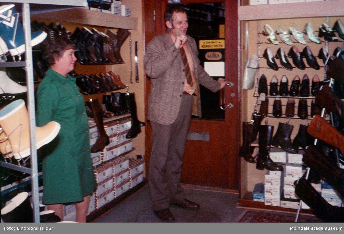 Märta Sjöberg tillsammans med en man, eventuellt försäljare, i Rasmussons skoaffär med adress Kvarnbygatan 4 vid Gamla Torget i Mölndal, 1970-tal.  För mer information om bilden se under tilläggsinformation.