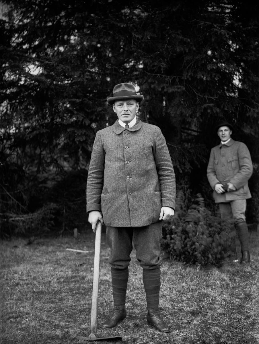 """""""E. Storm, Tärnsjö med hackan och en åskådare bakom"""", vid Nybron, Altuna socken, Uppland 1919"""