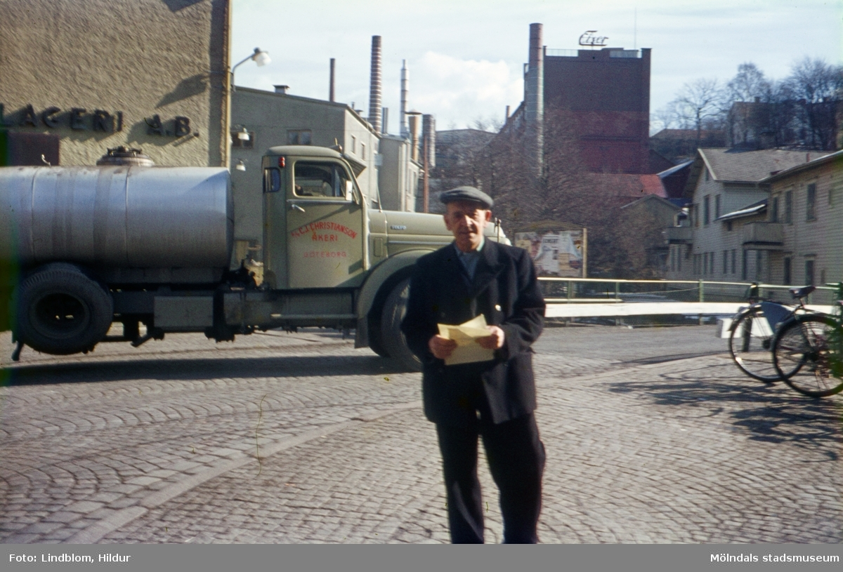 En man fotograferad framför en tankbil vid Forsebron i Mölndal, 1960-tal. I bakgrunden till vänster ses del av gaveln till huset Kvarnbygatan 6, byggnad tillhörande SOAB. I mitten ses Stora Götafors och till höger Götaforsliden 1-5.  För mer information om bilden se under tilläggsinformation.