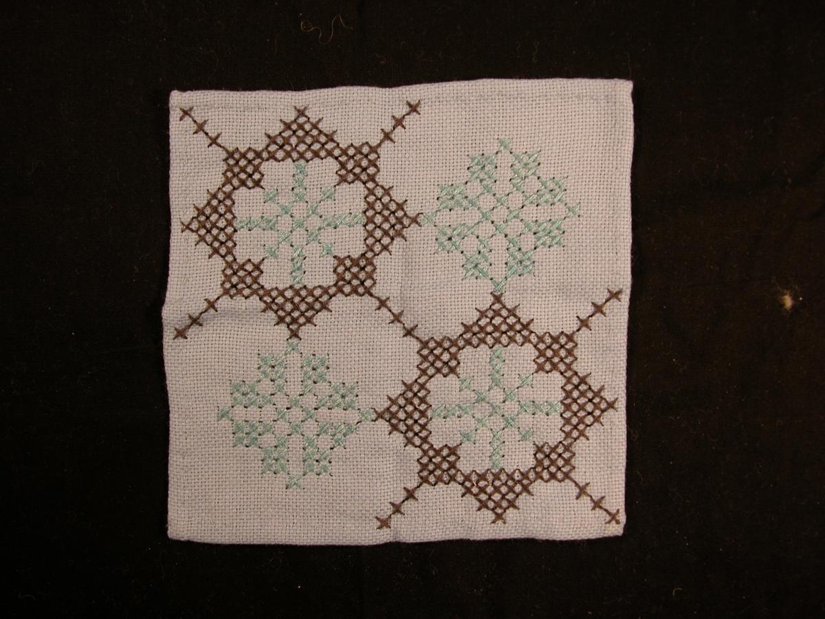 Dominerande svartgrå saum, der to firkantar heng saman diagonalt på stoffet. Turkisgrøn saum inni desse firkantane, samstundes som det er turkisgrøne firkantar på motsatt side av dei svartgrå.