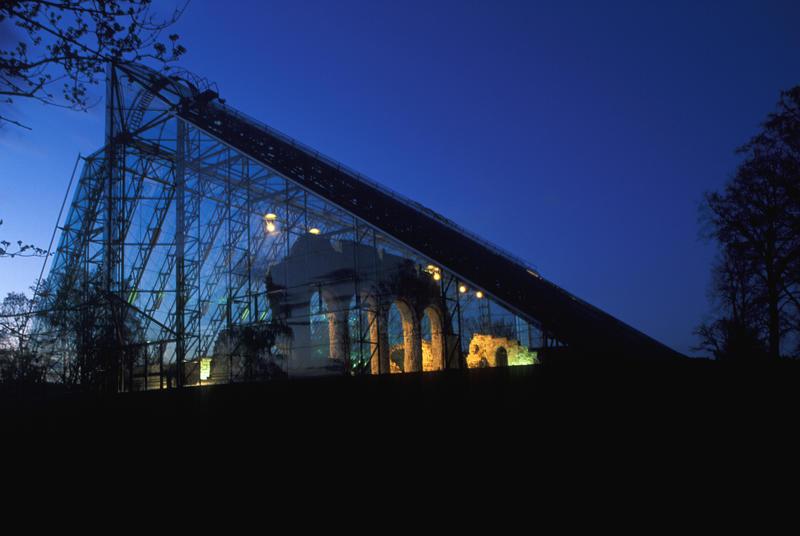 Domkirkeruinen under vernebygget i glass og stål er delvis opplyst og delvis i silhuett mot en mørkeblå kveldshimmel. (Foto/Photo)