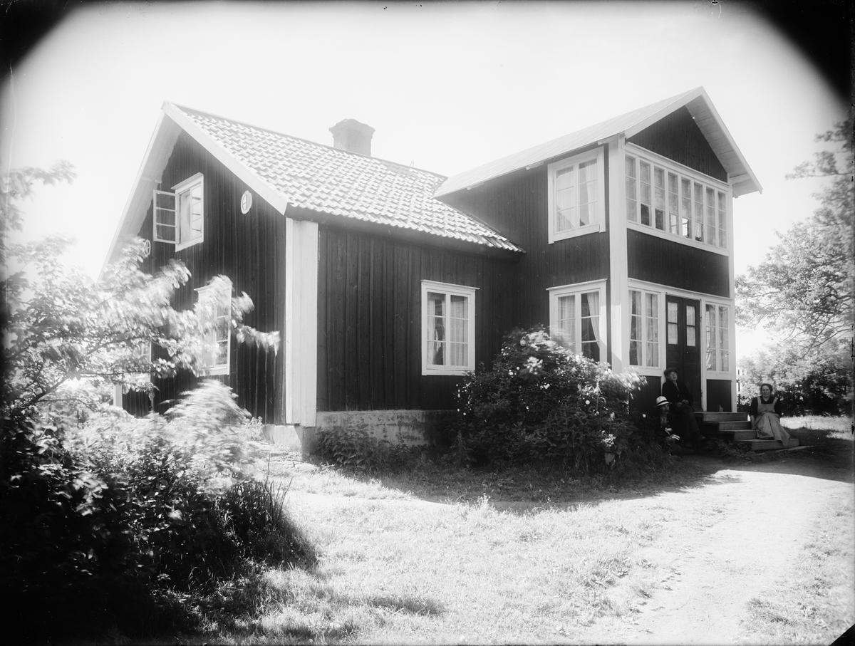 Man, kvinna och barn sitter på trappan, Raggarön, Börstils socken, Uppland