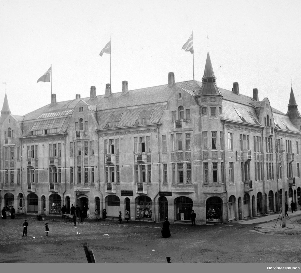 Grand Hotell nr. 2 på Torget på Kirkelandet i Kristiansund, her sett med fasade mot torget og Bernstorffstredet. Historie: Natten til 8. november 1907, kl. 04:00 ble det slått brannalarm. Nattevakten hadde oppdaget at det brente ved byens første Grand Hotell og mer enn 300 menn kom raskt til stede, inkludert fem fra sjødampsprøyta. Brannen som hadde startet i hotellets vedbu, spredte seg svært raskt, og det ble snart klart at det store trekomplekset ikke stod til å redde. To mennesker mistet livet i brannen. Disse var søstrene Anna og Augusta Sørensen som drev motehandel i første etasje av hotellet. Den flotte trebygningen i utført sveitserstil var nå blitt slukt av flammene.  Ikke lenge etter besluttet Nils Nilsen å bygge et nytt hotell på den samme tomten. Arkitekten ble Kristen Tobias Rivertz fra Kristiania, som stod bak flere andre kjente bygg i Kristiansund, som f.eks. Festiviteten og Norges Bank.   Det nye hotellet som ble bygd i jugendstil, ble oppført med teglstein, hvor ytterveggene var av Trondheimsk hulmur, som var pusset med sement. Bygningen kostet litt over 200.000 kroner, eksklusive tomt og montering. Oppføringen av hotellet var det murmester Olsen & Michalsen som utførte etter Rivertz tegninger og ledelse.  I hotellet fant vi bl.a. følgende romplan: 1. etasje inneholdt 11 forretninger. I 2. etasje finner vi 8 hotellrom, forhall, leserom, spisesal, røykerom, to mindre salonger, eierens privatleilighet samt kjøkken, anretning, oppvaskkum, spiskammer, koldkjøkken m.v. I 3. etasje finner vi 17 hotellrom samt 1 bad, mens i loftetasjen finner vi et fotografisk atelier, en større festsal, 7 hotellrom, samt rom for betjeningen og bryggerhus. Totalt var det 32 gjesterom ved det nye hotellet, og disse varierte fra 4 x 5 til 6 x 10 meter i areal.  Hotellet stod ferdig januar 1909.  Driften av hotellet gikk godt frem mot første verdenskrig, og i 1913 gikk Nilsen i gang med å utvide hotellbygningen med to fløyer mot øst og sør, slik at den kom til å danne et helt