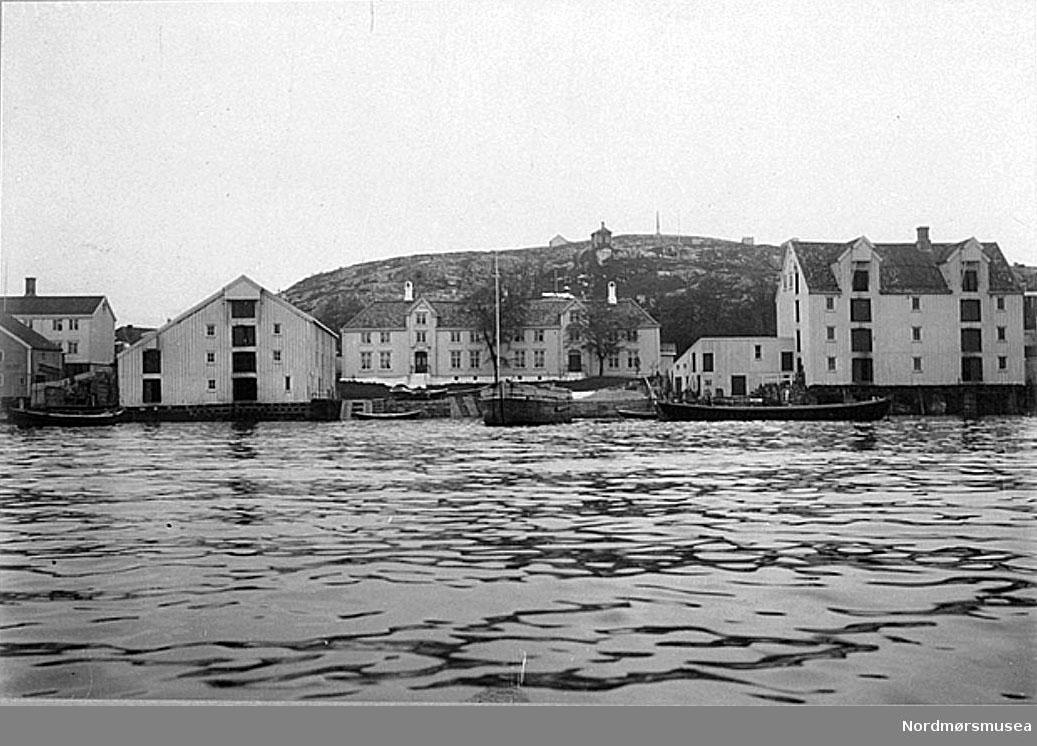 """""""Lossiusgården"""", matrikkel nr. 322, Skippergaten 15-17, fotografert  1911. W. Lund skriver samtidig: Midt på bildet sees våningshuset, som eies og bebos av konsul Lorentz A. Lossius (f. 1875). Om denne gård meddeler den 83-årige frk. Thronæs følgende som hun husker tilbake til  1830-40-årene: """"Lossiusgården kaltes før i tiden av gamle folk for """"Tordenskjoldgården"""".  Vånegården har i det ytre ikke undergått noen forandring i min tid.  Våningshusets fasade vendte som nå mot sjøen.  Foran fasaden var en stor plen og foran denne igjen en kai (""""klopp"""")  av tre med trapp til sjøen og med båtopptrekk (""""lunner""""), alt til gårdens eget bruk.  Bryggen ( «pakkhuset») sees til venstre på bildet.  Bak våningshuset, like inntil huset og mellom dette og veien, lå to mindre blomsterhaver.  Lengre bak huset på den andre side av veien lå en stor have med høye trær. I nærheten av våningshuset lå et stabbur som hørte til gården.  I dette stabbur ble det oppbevart  matvarer for husets eget bruk og til bruk for husets skip.  Flere brønner lå i den store hagen på baksiden.  Til gården hørte engløkker som lå langt utover Innlandet, og her lå høylåver og fjøs for gårdens mange krøtter.   Den fineste inngangen til våningshuset var den som sees til venstre på husets fasade mot sjøen.  Fra denne inngang går en passasje tvers gjennom huset med utgang mot bakhagen.  Selskapsværelsene lå til venstre for denne gang. I  første etasje lå ballsalen, hvor man også spiste ved store middager; ovenpå var det toaletttværelser for gjestene.  Kontorene var i høyre del av bygningen.  Døren som sees til høyre på husets fasade mot sjøen fører også inn til en gang som går tvers igjennom huset med utgang mot hagen på den andre siden. Ildhuset (grovkjøkken, klesvask, slakting, brygging, baking etc.) lå i enden av våningshuset (på 2000-tallet en del av kontoret) under samme tak som våningshusets øvrige rom, mens det egentlige kjøkkenet ligger mer midt i samme bygning ut mot baksiden.  Alle store kjøpmannsgårder her"""