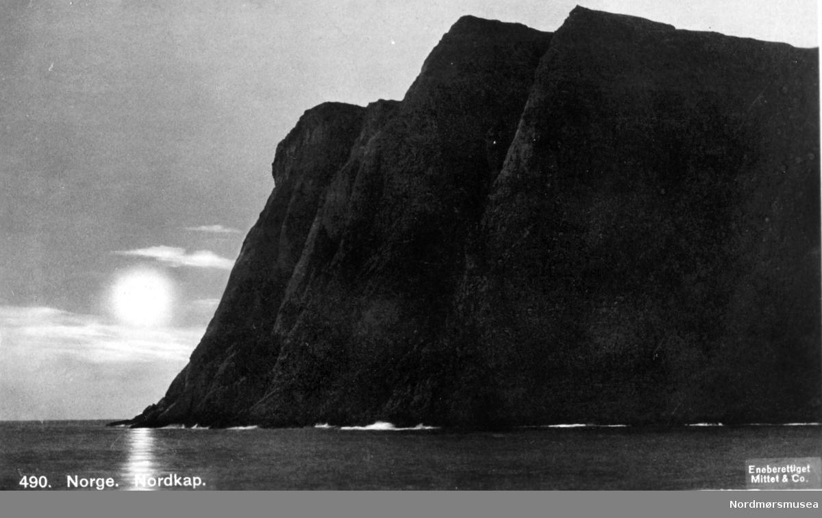 """Nordkapp fra sjøsiden, med midnattsolen i bakgrunnen. Postkortet er stemplet """";Eneberettiget Mittet & Co.""""; fra Nordmøre Museums fotosamlinger."""