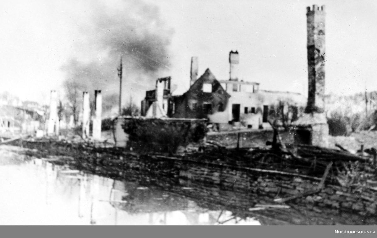 Foto fra et tettsted i ruiner. Kan det være fra brannen på Øra i Surnadal kommune i 1938, eller er det fra krigen noen år senere og en annen plass i Møre og Romsdal? Datering er ukjent, men muligens omkring 1938 til 1943. Se serie fra reg. nr. KMb-1987-005.2923 til KMb-1987-005.2941.  Tyskernes bombing av Bergen i juni 1940.Fra Nordmøre museums fotosamlinger.
